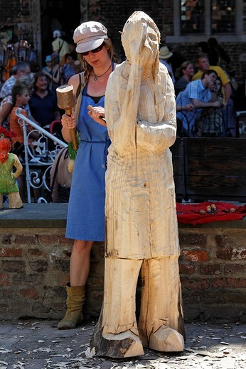 Young sculptress working on a life sized lime wood sculpture, traditional craftsmans market, Flachsmarkt Burg Linn, Krefeld, Lower Rhine, North Rhine_Westphalia, Germany, Europe : Stock Photo