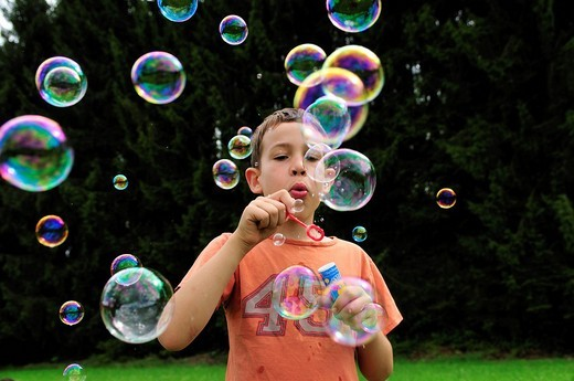 Stock Photo: 1848-140063 Boy blowing many colourful bubbles