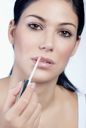 Stock Photo: 1848-140953 Young woman applying lip gloss, looking directly at the viewer, beauty