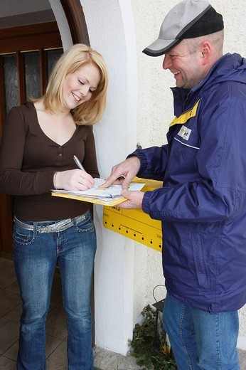Stock Photo: 1848-141882 Woman signing for a parcel delivered by a postman, mailman