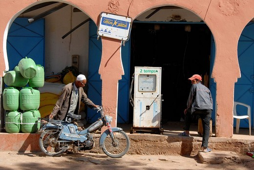 Stock Photo: 1848-143180 Oriental flair motorcyclist gets gas at old fuel station Foum Zguid Morocco