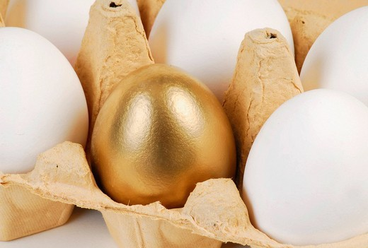 Golden egg in a carton of white eggs : Stock Photo