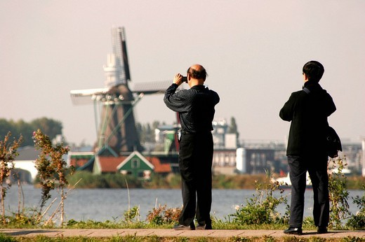 Japanese tourists take photos of a windmill in the Museum Zaanse Schans, Zaandam, Netherlands, Europe : Stock Photo
