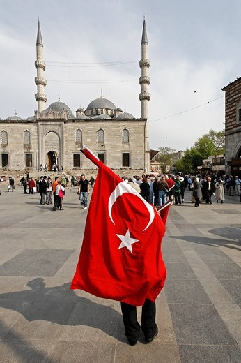 Street vendor carries large Turkish national flag, square in front of the New Mosque, Yeni Cami, Eminoenue, Istanbul, Turkey : Stock Photo