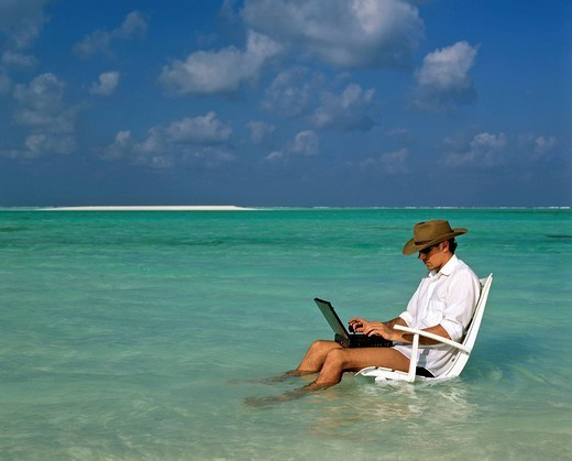 Young man with laptop sitting on deck chair, work and relaxation, vacation and stress, Maldives, Indian Ocean : Stock Photo