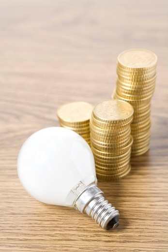 Stock Photo: 1848-145687 Lightbulb and stacks of coins
