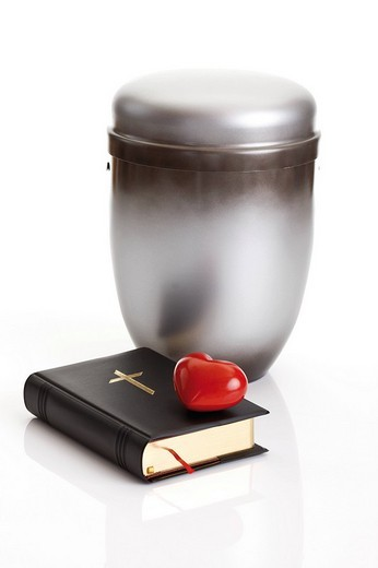 Silver_grey urn and heart placed on a Bible : Stock Photo