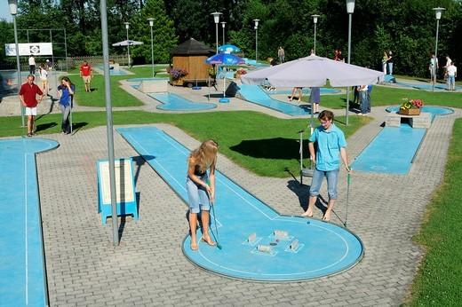 Young couple playing mini golf, county of Muehldorf, Upper Bavaria, Germany, Europe : Stock Photo