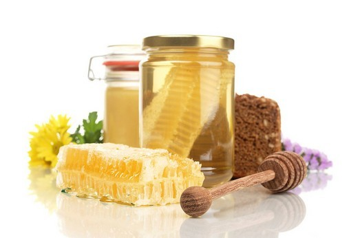 Honey jars with honeycomb, whole_grain bread, honey dipper and flowers : Stock Photo