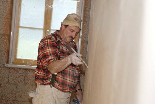 Plasterer at work, wave_like plaster, house construction, brickwork, interior works, plastering works : Stock Photo