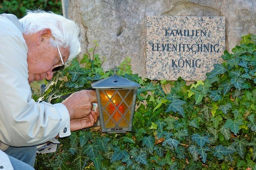 Stock Photo: 1848-148995 Man lighting a candle at the church yard on All Saints´ Day, Klosterneuburg, Austria