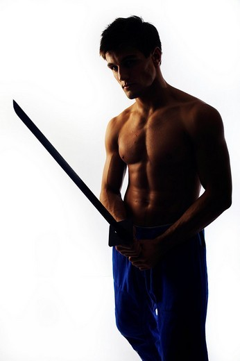 Young fighter with bare upper body holding a wooden sword, backlight : Stock Photo
