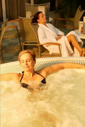 Whirlpool, two young women relaxing : Stock Photo