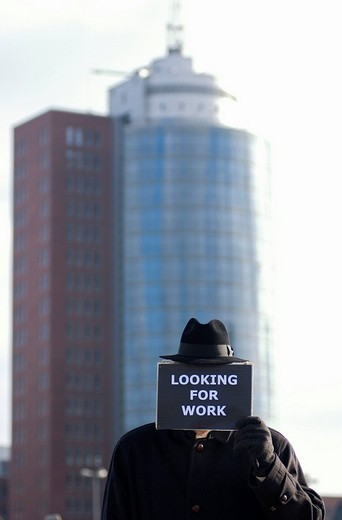 Man holding a sign with the message, Looking for work, symbolic image for the economic crisis : Stock Photo