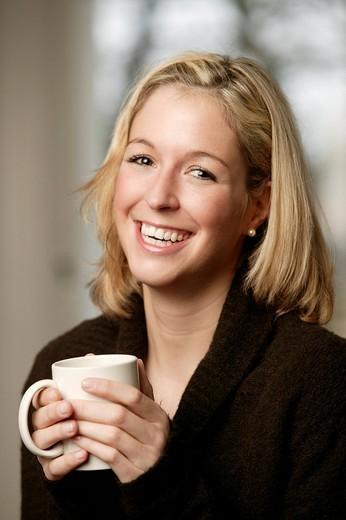 Smiling young blonde woman in a dark sweater holding a mug : Stock Photo