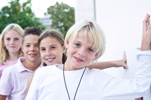 Four friends standing behind each other, in the schoolyard, laughing : Stock Photo