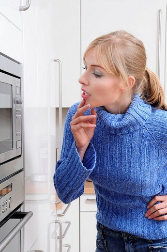 Women cooking with a microwave in a modern kitchen : Stock Photo