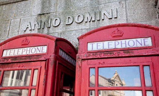 Red telephone boxes in front of lettering anno domini, Penzance, Cornwall, England, United Kingdom, Europe : Stock Photo