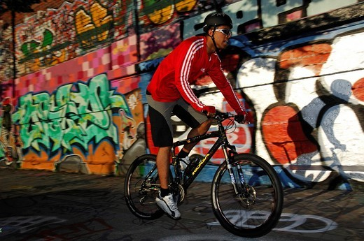 Stock Photo: 1848-158205 Mountainbiker in front of graffiti wall