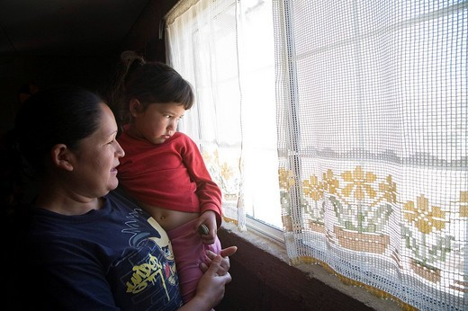 Mother and daughter at the window of their new house after gang members burned down their old home when one of the children refused to sell drugs for them, the house was subsequently built by Habitat for Humanity, Solidaridad colonia, Nogales, Sonora, Mex : Stock Photo
