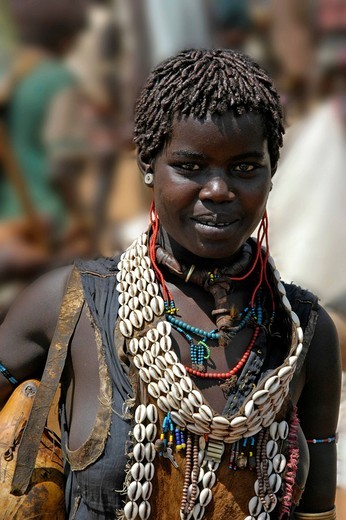 Stock Photo: 1848-159060 Young woman wearing cowry shell necklaces and various adornment market of Keyafer Ethiopia