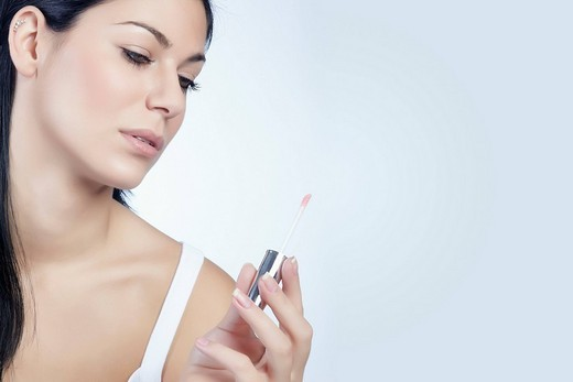 Young woman looking at her lip gloss in her hand, beauty : Stock Photo