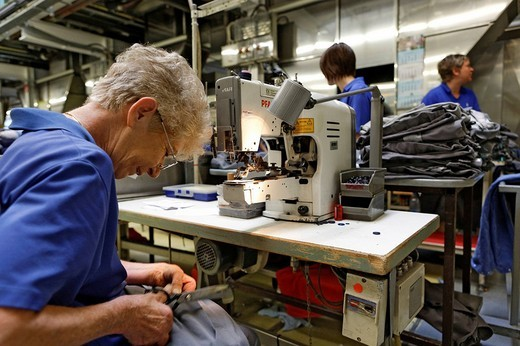 Stock Photo: 1848-164748 Yeter Sebe sewing damaged rental clothing in the blue section of an industrial laundry, Bardusch Uniform Rental & Laundry Services, Textil_Mietdienst Bardusch GmbH in Ettlingen, Baden_Wuerttemberg, Germany, Europe