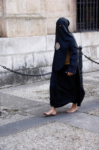 Penitent dressed in black robe nazareno on their way to the Holy Week procession, Semana Santa, Seville, Andalusia, Spain : Stock Photo