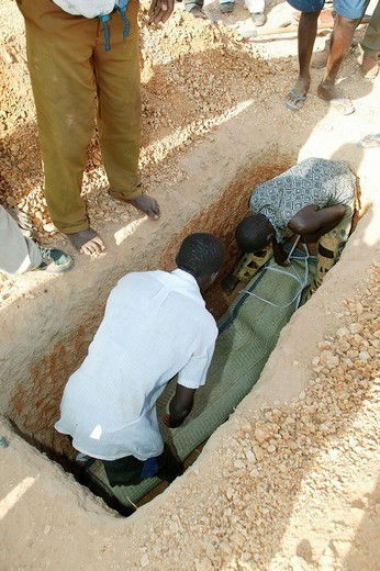 Body of a woman who died of HIV/AIDS being lowered into a grave during her funeral, Garoua, Cameroon, Africa : Stock Photo