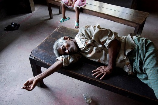 A patient sleeping while waiting in an outpatient clinic run by an aid organization in the Slums of Howrah, Hooghly, West Bengal, India : Stock Photo