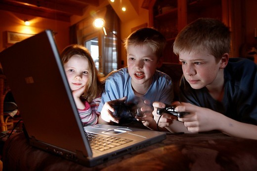 Stock Photo: 1848-166323 Siblings, 7, 11, 13 years old, with laptop computer in the living room, playing a car racing computer game