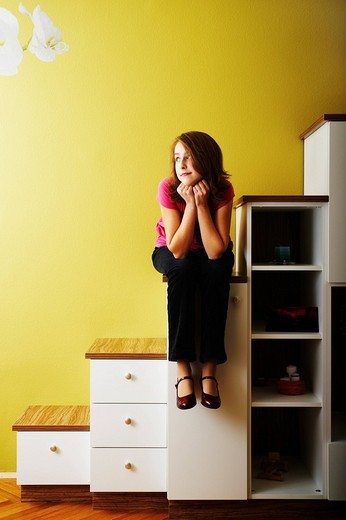 Young girl sitting on the steps of a chest of drawers : Stock Photo