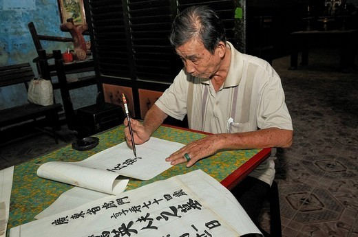 Old man, calligrapher at work, sitting at a table making a calligraphy, Vietnam, Southeast Asia : Stock Photo