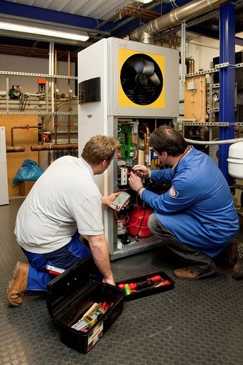 Specialist lecturer and Master Craftman for plumbing student in the heating, ventilating, and air conditioning, HVAC laboratory, controlling a heat exchanger in an air conditioner, Master Craftman School of the Chamber of Small Industries and Skilled Trad : Stock Photo