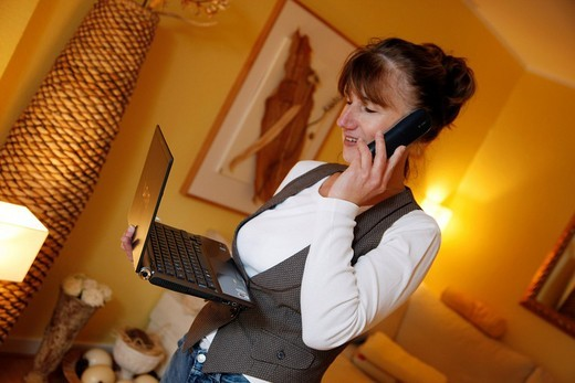 Woman, 45 years, on the phone and working on a laptop computer in her apartment : Stock Photo