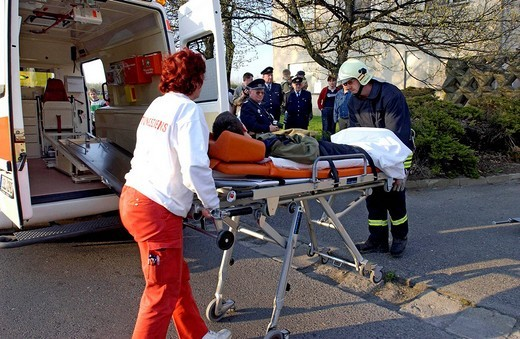 Emergency drill, burn victim is being cared for on a stretcher : Stock Photo