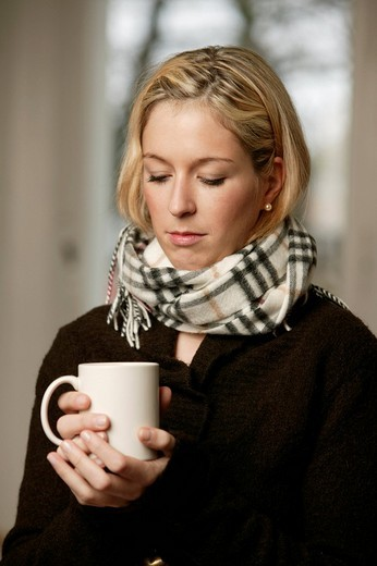 Stock Photo: 1848-171460 Blonde woman in dark sweater holding a mug