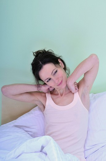 Portrait of an adult woman, alone, relaxing, waking up in the bed of the sleeping room : Stock Photo