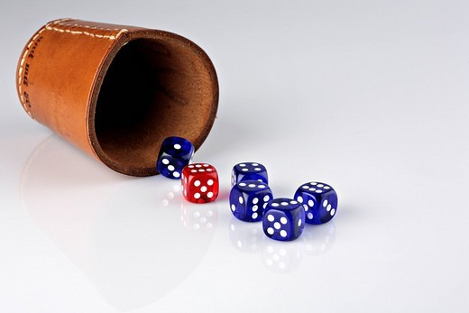 Five blue and one red dice beside a dice cup : Stock Photo
