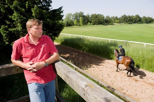 Racehorse trainer Werner Glanz observing his jockeys during training on the training track of Munich Racecourse in Munich_Riem, Munich, Bavaria, Germany, Europe : Stock Photo
