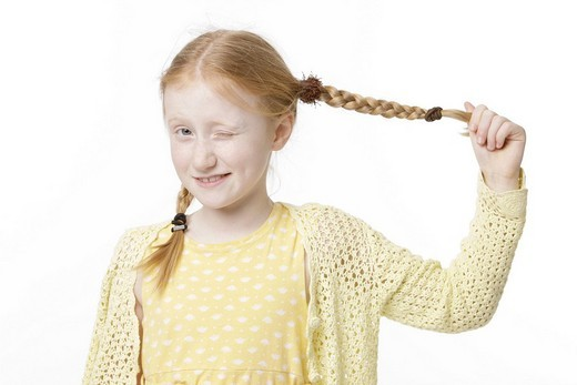 Eight_year_old girl wearing a yellow dress pulling her pigtail : Stock Photo