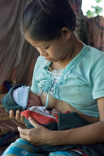 17 year old mother breastfeeding her baby, Kway Nya Ou village, IDP_Area bordering Thailand near Maesot, Birma : Stock Photo