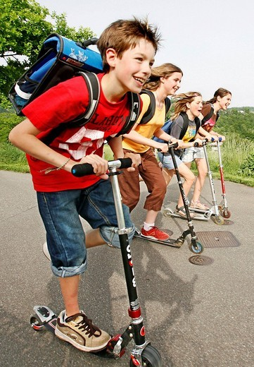 Stock Photo: 1848-173999 School children, boys and girls, riding kick scooters, push scooters on the way from school, Basel, Switzerland, Europe