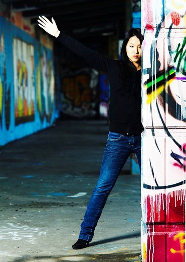 Young Asian girl in rapper pose between walls with graffiti : Stock Photo