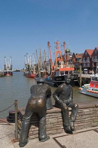 Bronze sculpture by of Old Fisherman and Young Fishermen in the port Neuharlingersiel, in the back shrimp boats, North Sea, East Frisia, Lower Saxony, Germany, Europe : Stock Photo