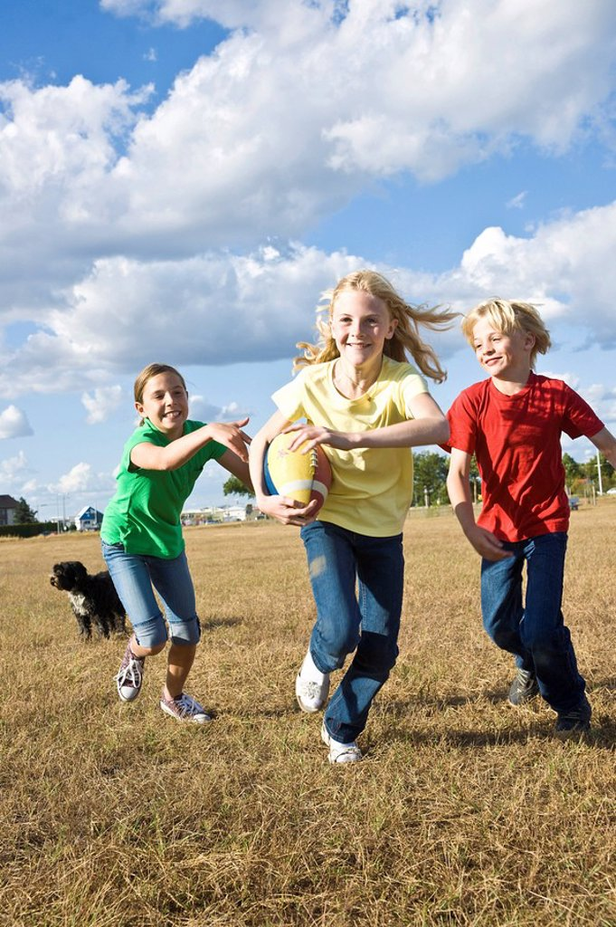 Stock Photo: 1848-176655 A group of laughing children playing with a dog and a football
