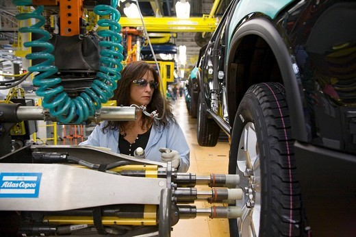 Stock Photo: 1848-178082 A worker tightening lug nuts on a tire on the assembly line at a General Motors assembly plant which produces Buick, Saturn, and GMC vehicles, Lansing, Michigan, USA