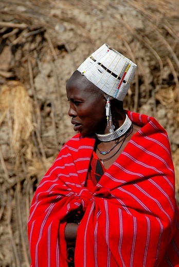 Masai woman wrapped in a red cloth and wearing a white head hat, Serengeti, Tanzania, Africa : Stock Photo