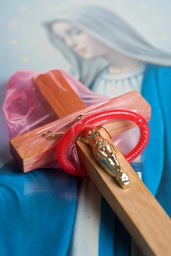 Condom pulled over a cross, in front of a picture of the Madonna : Stock Photo