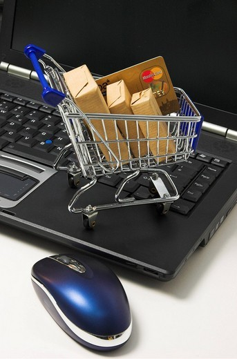 Online shopping, a shopping cart filled with parcel and a credit card standing on the keyboard of a notebook computer : Stock Photo